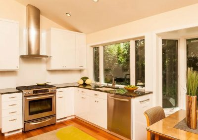 Kitchen with green marble countertops and white cabinets 2