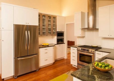 Kitchen with green marble countertops and white cabinets